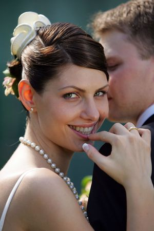 Portrait of newlywed smiling bride leaning on grooms shoulder. photo