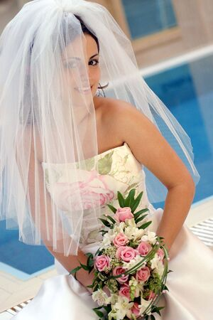 Smiling young bride wearing veiled white dress holding bouquet of flowers. Stock Photo - 5176220