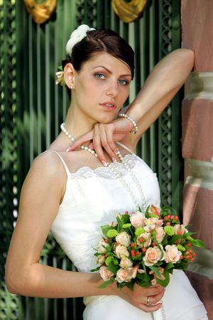 half body: Half body portrait of beautiful young adult bride in white dress holding bouquet of flowers.