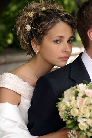 Pretty newlywed bride leaning on husbands shoulder with bouquet. photo
