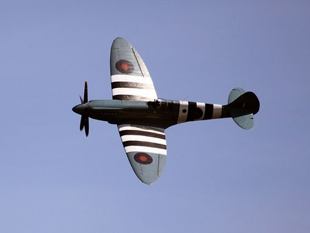 aeronautical: Spitfire aircraft in flight with blue sky background.