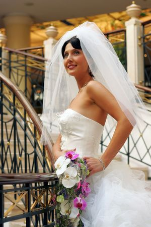 Smiling bride wearing white wedding dress walking upstairs with bouquet. Stock Photo - 5313878