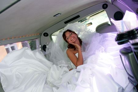 Happy young adult bride in wedding car limousine.