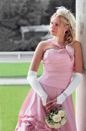 Beautiful young bride wearing pink dress and holding bouquet of flowers. photo