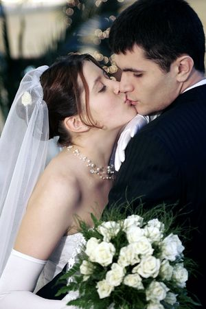 mladistvý: Young newlywed couple kissing pasionately, bride holding bouquet of flowers.