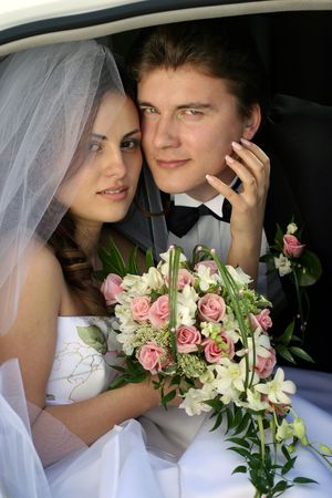 Smiling newlywed young girl in wedding car limousine doorway with bouquet of flowers. photo