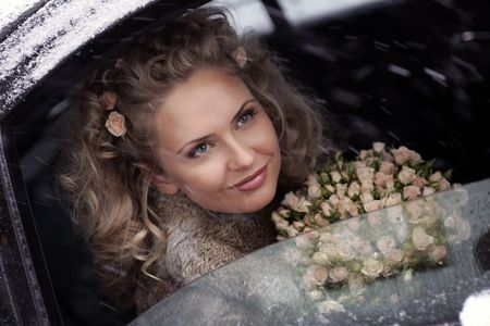 wintry: Smiling young adult bride holding bouquet of flowers looking out of limousine window on snowy, wintry day.
