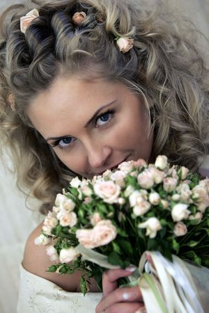 Young adult bride smiling behind bouquet of flowers. Stock Photo - 5435612