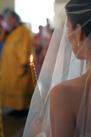 Rear view of bride wearing white wedding dress and holding lighted candle walking behind orthodox priest. photo