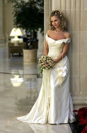 the happy bride: Full length portrait of beautiful young adult bride leaning against stone column holding bouquet of flowers.