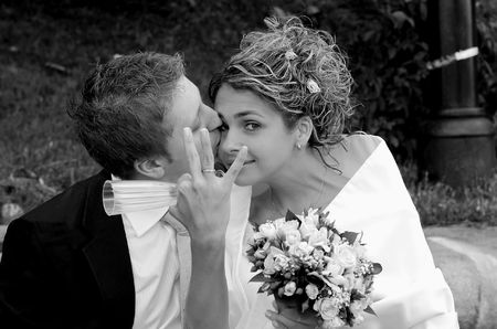 Newlywed groom kissing bride who is holding gls and showing off wedding ring, outdoors. photo