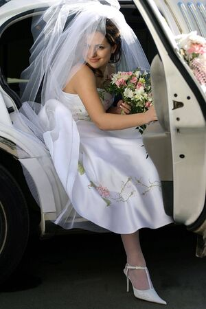 exits: Smiling bride with bouquet exiting wedding car limousine door with sunlight on veil.