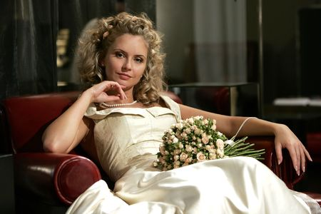 Pretty young adult bride relaxing in red chair with bouquet of flowers. Stock Photo - 5426791