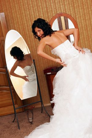 Rear view of bride trying on wedding dress and looking in mirror. photo