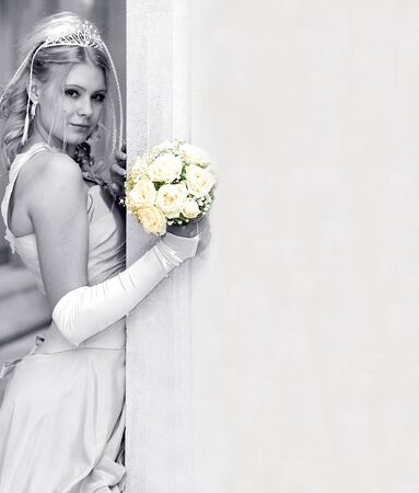 the happy bride: Attractive blond young adult bride leaning on wall with copy space.