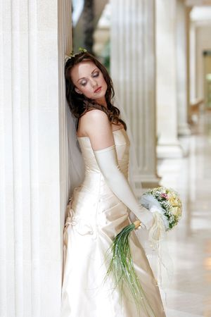 Pretty young adult bride wearing wedding dress and holding bouquet leaning on marble column, thoughtful expression. Stock Photo - 5507741