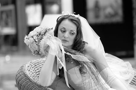 Fashionable young bride wearing white dress with veil holding bouquet, thoughtful expression. Stock Photo - 5507740