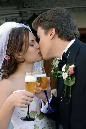 Half body portrait of young adult newlywed couple kissing and toasting each other with drinks. photo