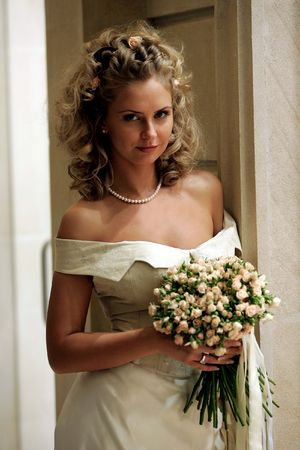 Portrait of smiling young adult blond brid holding bouquet of flowers. Stock Photo - 5553678