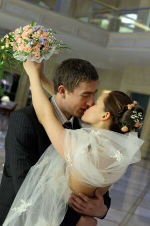Half body portrait of passionate newlywed couple kissing and embracing. photo