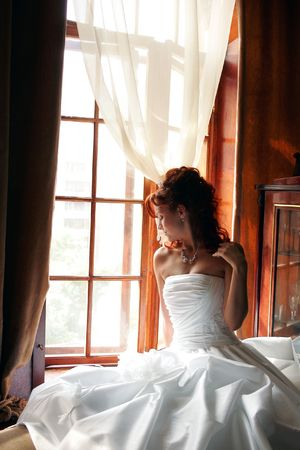 Young adult bride wearing white wedding dress sat by window in sunlight. Stock Photo