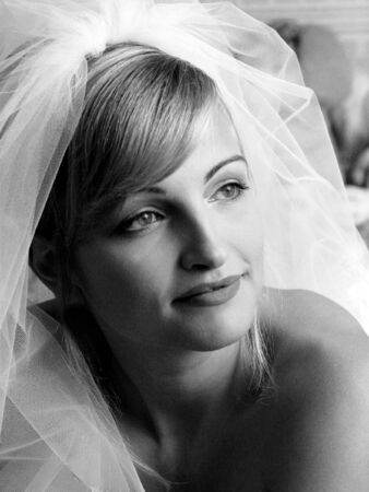 Black and white portrait of young adult bride wearing wedding dress veil. photo