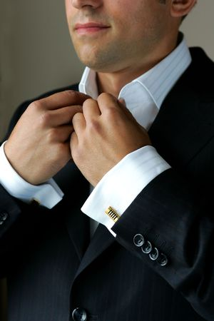lapels: Portrait of young adult businessman buttoning short, studio background.