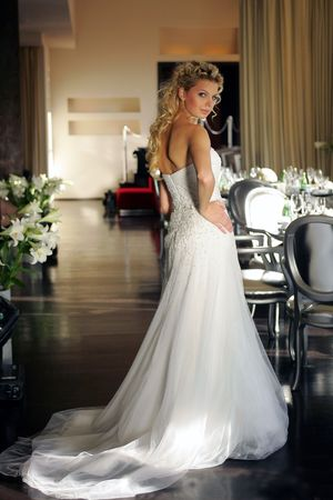 Blond young adult bride looking over shoulder at wedding reception indoors. photo