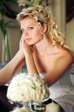 contemplates: Half body portrait of pensive young adult blond bride with bouquet in foreground.