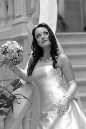 half body: Half body portrait of beautiful young adult bride holding bouquet of flowers, stood in stairs.