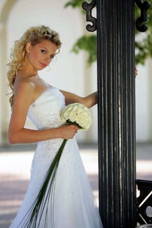 Half body portrait of young adult blond bride holding bouquet and smiling. photo
