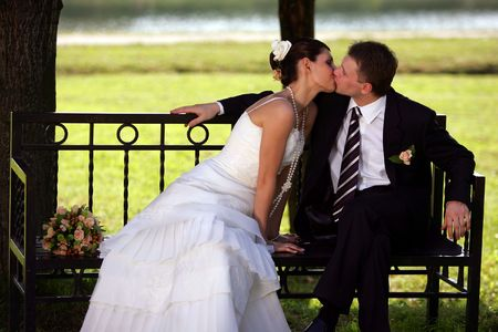 Closeup of happy newlywed couple kissing on park bench outdoors. photo