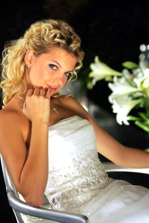Half body portrait of attractive young blond bride sat in chair with black background. photo