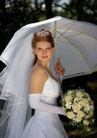 Half body portrait of young bride sheltering under parasol outdoors. photo