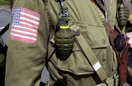 Details of American World War two GI soldier wearing army uniform with hand grenades and pistol. photo