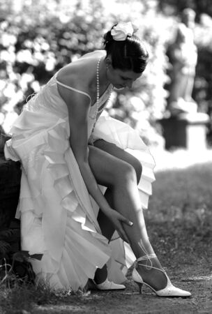Smiling bride sat outdoors adjusting stockings. photo