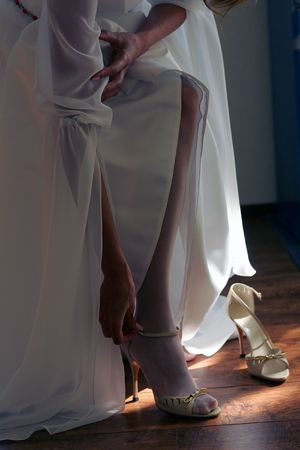 Closeup of young bride in white wedding dress putting on high heeled shoes. photo