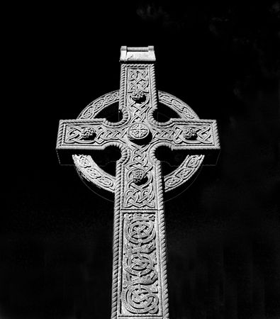 pagan cross: Low angle black and white view of decorative stone Celtic cross with black background.
