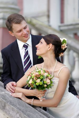 Happy newlywed couple looking lovingly at each other outdoors. photo
