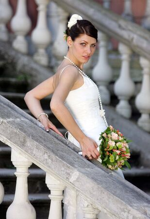 Half body portrait of pretty bride with bouquet of flowers on stone stairs outdoors. photo