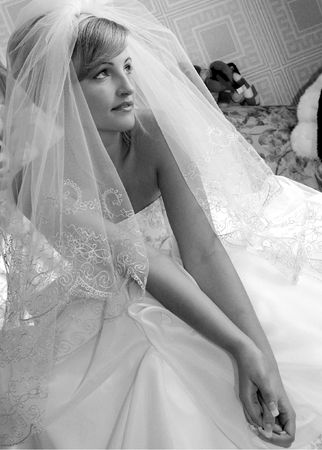 Three quarter black and white images of pretty young adult blond bride in wedding dress with veil. photo