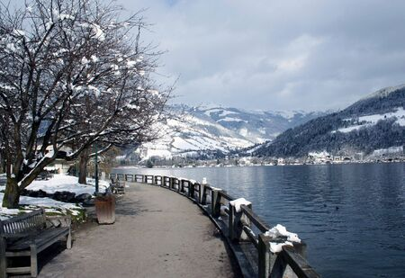 snow capped mountain: Scenic view of path around lake with snow capped mountains in background, Zeller See, Zell am Zee, Austria. Stock Photo