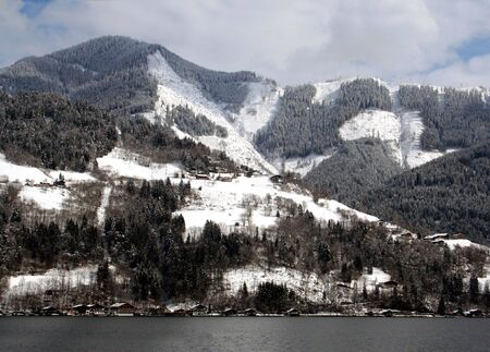 forested: Scenic view of alpine lake and forested mountains in winter, Zell am Zee resort, Austria.
