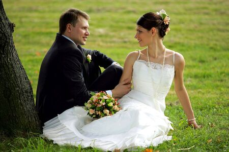 Happy young newlywed couple sat under tree in countryside. photo