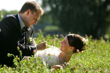 Newlywed young couple romancing in summer meadow outdoors. photo