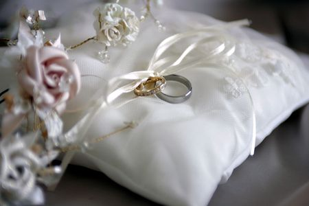 showed: Closeup of bride and groom wedding rings on white cushion. Stock Photo