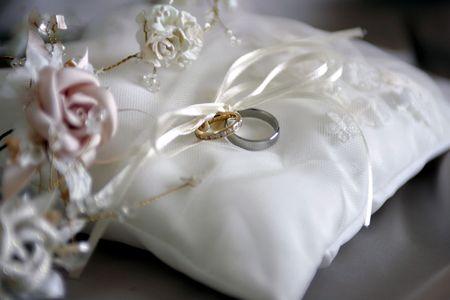 Closeup of bride and groom wedding rings on white cushion. Standard-Bild