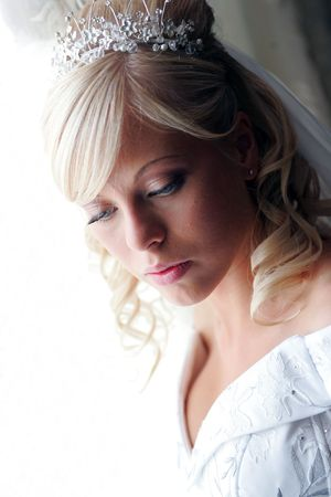 Portrait of pretty young blond haired adult bride with tiara looking down, with copy space. photo