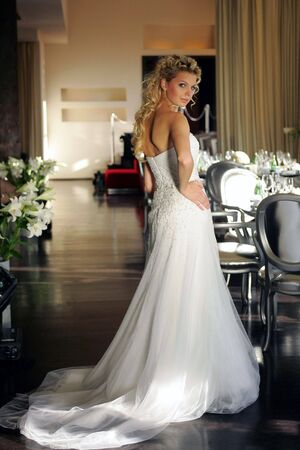 Full body portrait of blond haired young bride posing in white wedding dress.
