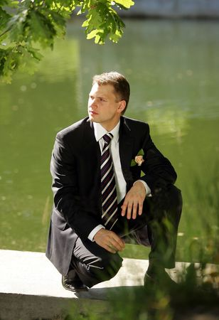 Handsome young male groom kneeling by lake in summer. photo